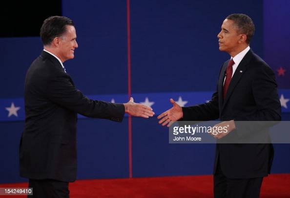Republican presidential candidate Mitt Romney and US President Barack Obama shake hands after a town hall style debate at Hofstra University October...