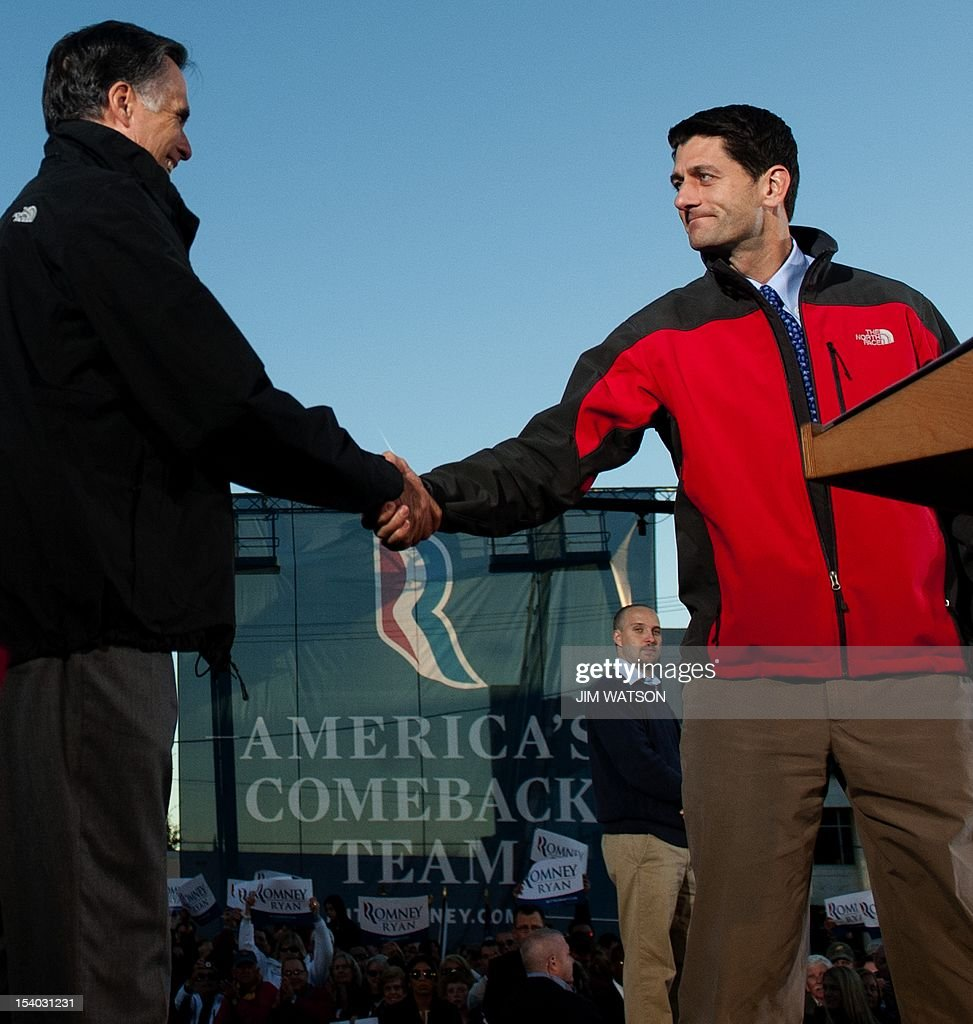 US Republican presidential candidate Mitt Romney (L) and US Republican vice presidential candidate Paul Ryan (R) shake hands while delivering remarks during a victory rally in Lancaster, Ohio, October 12, 2012. AFP PHOTO/Jim WATSON