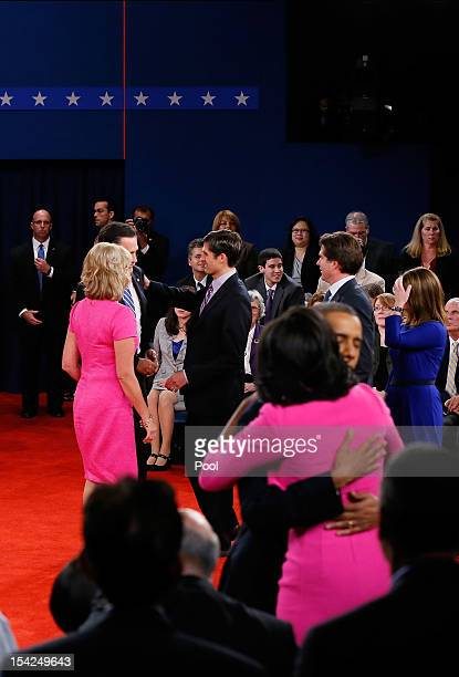 Republican presidential candidate Mitt Romney is greeted by his wife Ann Romney and son Matt Romney as US President Barack Obama hugs wife Michelle...