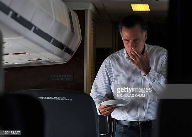 US Republican presidential candidate Mitt Romney licks his fingers while returning to his seat after making himself a peanut butter and honey...