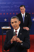 Republican presidential candidate Mitt Romney listens as US President Barack Obama answers a question during a town hall style debate at Hofstra...