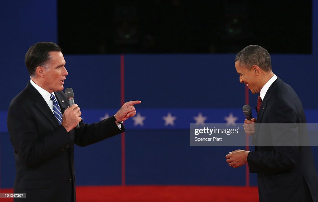 Republican presidential candidate Mitt Romney makes US President Barack Obama laugh during a town hall style debate at Hofstra University October 16...