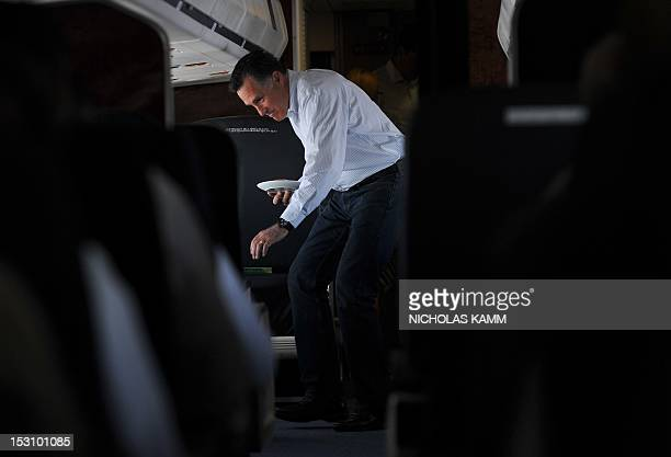 US Republican presidential candidate Mitt Romney returns to his seat after making himself a peanut butter and honey sandwich aboard his campaign...