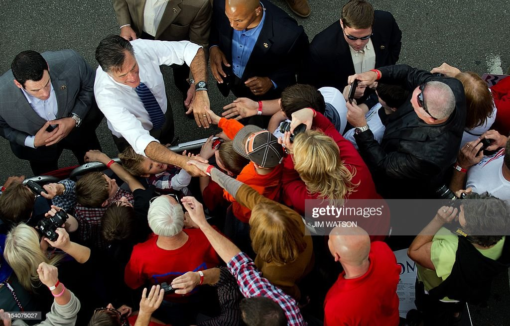 US Republican presidential candidate Mitt Romney (2nd L) shakes hands with supporters after delivering remarks at a victory rally Lebanon, Ohio, on October 13, 2012. AFP PHOTO/Jim WATSON