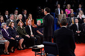 Republican presidential candidate Mitt Romney speaks as US President Barack Obama and audience members listen during a town hall style debate at...