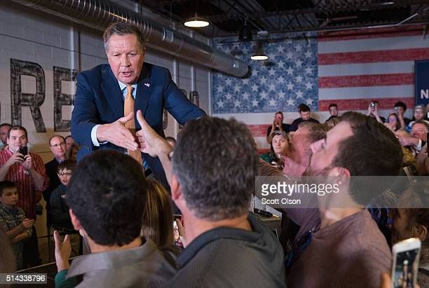 Republican presidential candidate Ohio Gov John Kasich greets supporters following a rally at the Lansing Brewing Company on March 8 2016 in Lansing...