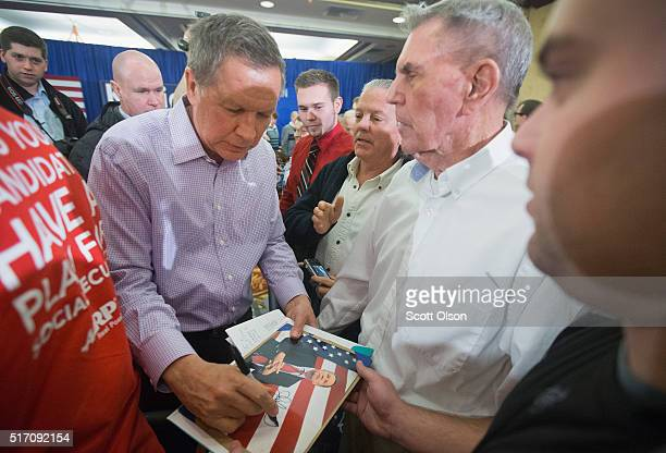 Republican presidential candidate Ohio Gov John Kasich greets guests following a campaign rally at the Crowne Plaza Milwaukee West hotel on March 23...