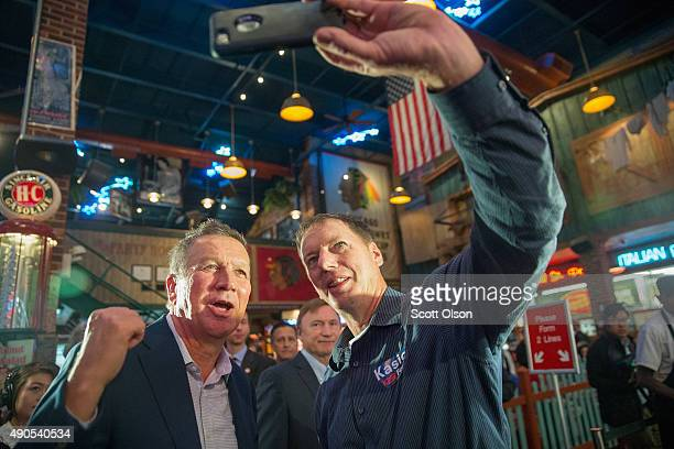 Republican presidential candidate Ohio Governor John Kasich poses for a selfie during a campaign stop at Portiillo's restaurant on September 29 2015...
