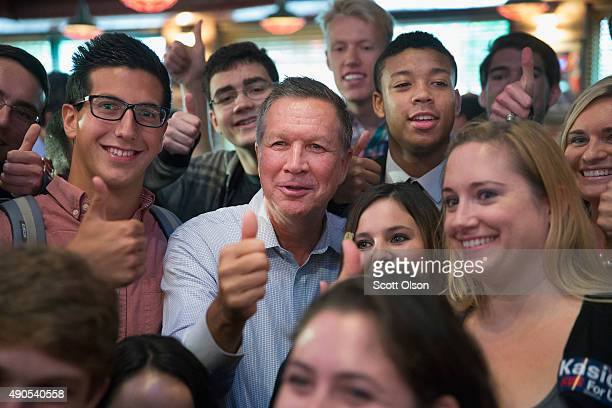 Republican presidential candidate Ohio Governor John Kasich poses for a picture with a group of College Republicans at Portiillo's restaurant during...