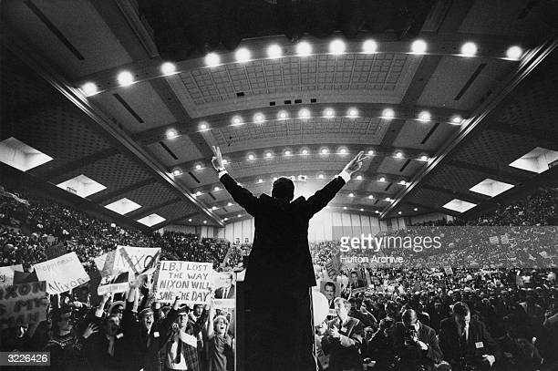 Republican presidential candidate Richard Nixon standing on stage with his back to the camera in front of an arena of supporters giving the victory...
