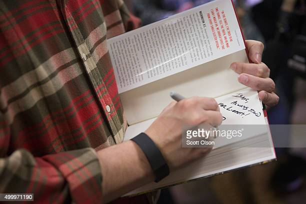 Republican presidential candidate Sen Ted Cruz autographs a book for a supporter during a campaign event at CrossRoads Shooting Sports gun shop and...
