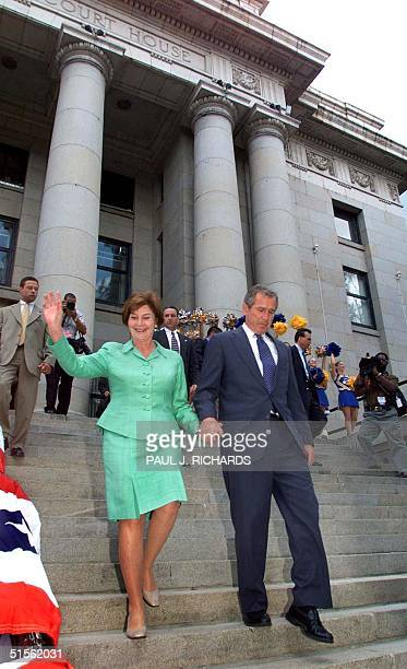 Republican presidential candidate Texas Gov George W Bush and his wife Laura walk down the steps of the Yavapai County Court House to address the...
