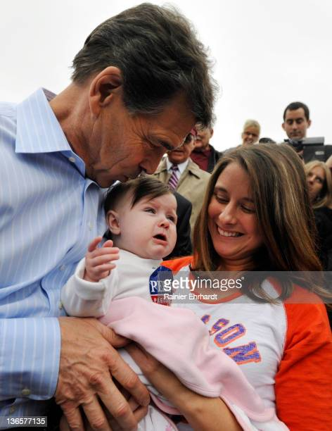 Republican presidential candidate Texas Gov Rick Perry kisses 7monthold Elaina Stephens as her aunt Candi Tennyson looks on during a campaign stop at...