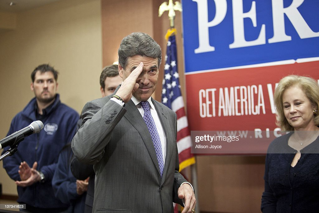 Republican presidential candidate, Texas Gov. Rick Perry salutes as his wife Antia looks on at Hyatt Place January 19, 2012 in North Charleston, South Carolina. Perry, who placed fifth in Iowa and New Hampshire, announced his withdrawal from the presidential race and endorsed former Speaker of the House Newt Gingrich.