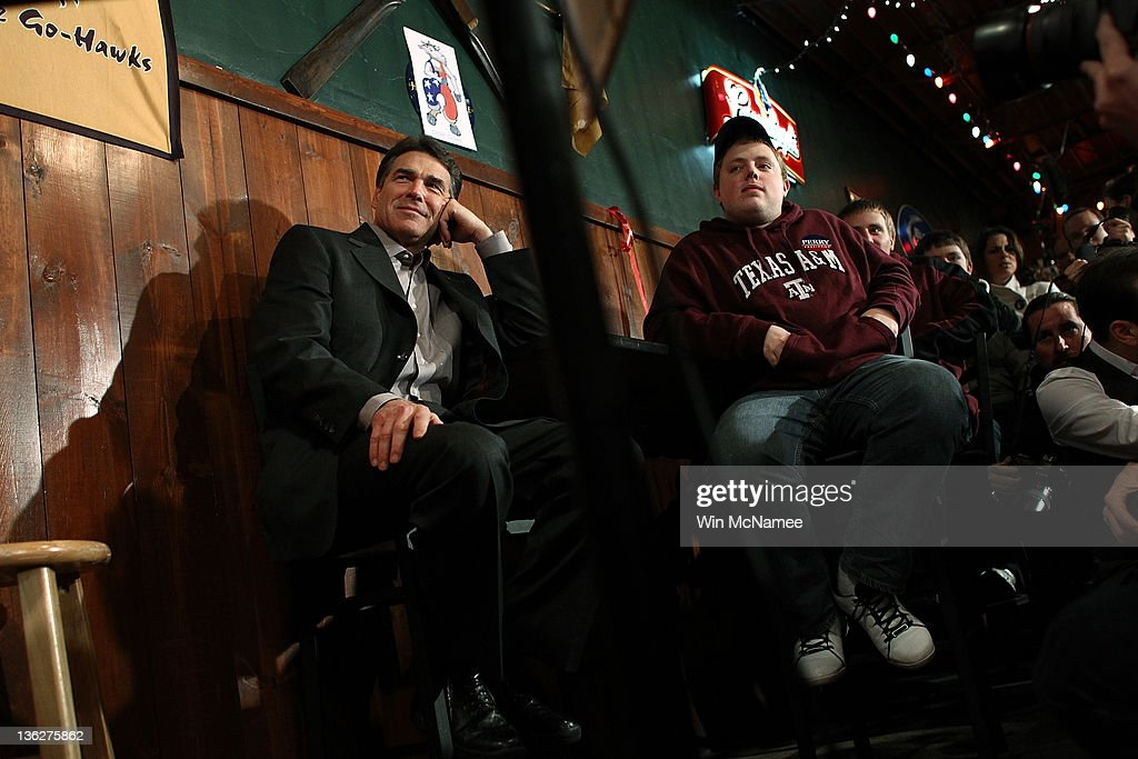 Republican presidential candidate Texas Gov. Rick Perry (L) waits to be introduced before speaking to Iowa voters at The Fainting Goat bar and restaurant December 30, 2011 in Waverly, Iowa. Four full days of campaigning remain before Iowans vote on January 3rd.