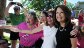 Republican presidential candidate US Rep Michele Bachmann greets supporters as she marches in a Fourth of July parade July 4 2011 in Clear Lake Iowa...