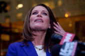 Republican presidential candidate US Rep Michele Bachmann wipes hair from her face while speaking to members of the media after meeting with Donald...
