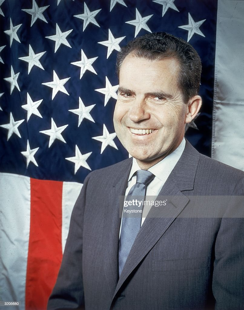Republican presidential candidate Vice-President <a gi-track='captionPersonalityLinkClicked' href=/galleries/search?phrase=Richard+Nixon&family=editorial&specificpeople=92456 ng-click='$event.stopPropagation()'>Richard Nixon</a> (1913 -1994) laughing as he poses in front of the stars and stripes.