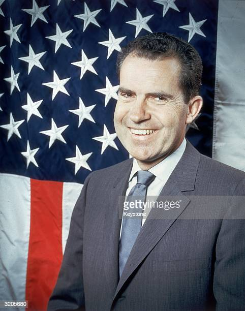 Republican presidential candidate VicePresident Richard Nixon laughing as he poses in front of the stars and stripes