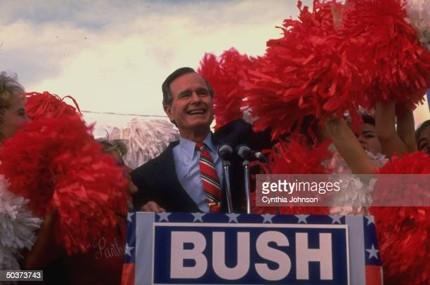 Republican presidential candidate VP George Bush addressing campaign rally framed by pom pomwaving cheerleaders