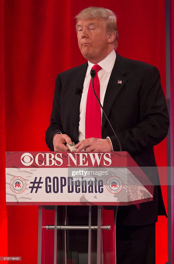 Republican presidential candidates Donald Trump holds a pack of Tic-Tacs during the CBS News Republican Presidential Debate in Greenville, South Carolina, February 13, 2016. / AFP / JIM WATSON
