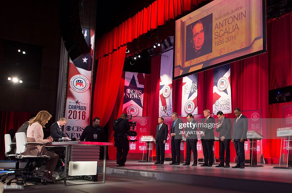 Republican presidential candidates hold a moment of silence for Associate Justice Antonin Scalia, who passed away earlier in the day, during the CBS News Republican Presidential Debate in Greenville, South Carolina, February 13, 2016. From left are: John Kasich, Jeb Bush, Ted Cruz, Donald Trump, Marco Rubio, and Ben Carson. / AFP / JIM WATSON