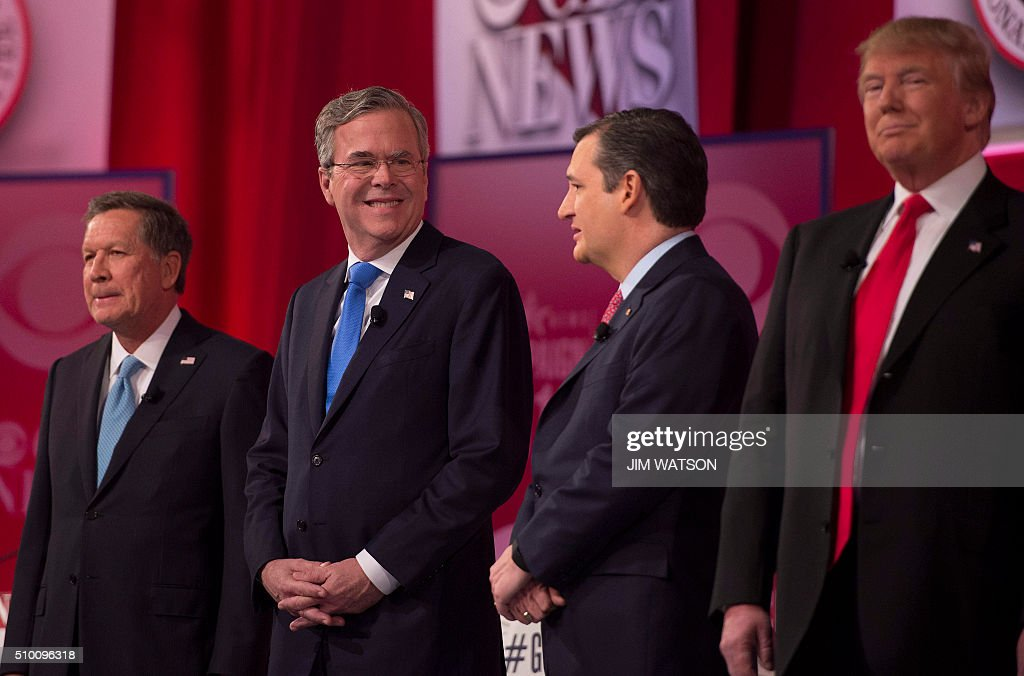 Republican presidential candidates John Kasich (L) and Donald Trump (R) look on as Jeb Bush (2nd-L) confers with Ted Cruz (2nd-R) during the CBS News Republican Presidential Debate in Greenville, South Carolina, February 13, 2016. / AFP / JIM WATSON