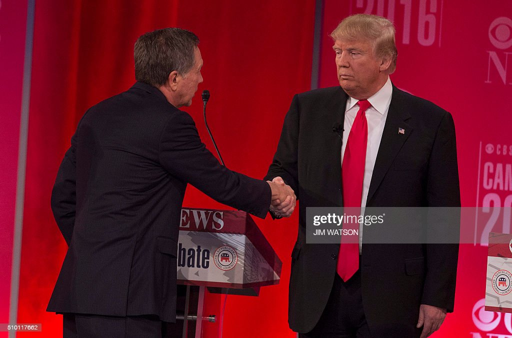Republican presidential candidates John Kasich (L) and Donald Trump (R) shake hands following the CBS News Republican Presidential Debate in Greenville, South Carolina, February 13, 2016. / AFP / JIM WATSON