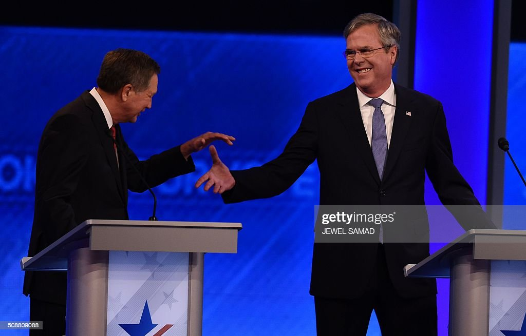 Republican Presidential candidates John Kasich (L) and Jeb Bush shake hands during the Republican Presidential Candidates Debate February 6, 2016 at St. Anselm's College Institute of Politics in Manchester, New Hampshire. Seven Republicans campaigning to be US president are in a fight for survival in their last debate Saturday before the New Hampshire primary, battling to win over a significant number of undecided voters. / AFP / Jewel Samad
