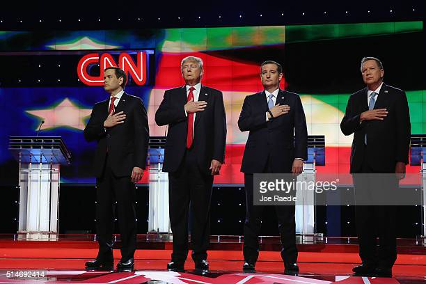 Republican presidential candidates Sen Marco Rubio Donald Trump Sen Ted Cruz and Ohio Gov John Kasich listen to the national anthem before the start...