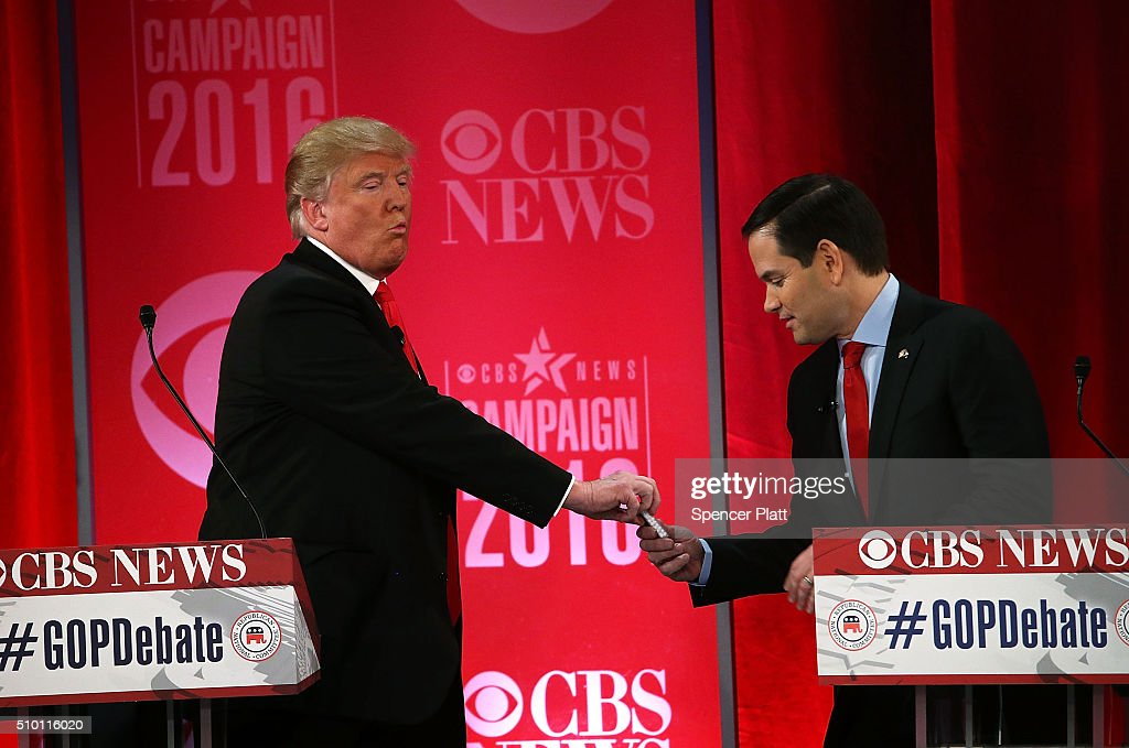 Republican presidential candidates Sen. Marco Rubio (R-FL) (R) is offered with candies by Donald Trump (L) during a break of a CBS News GOP Debate February 13, 2016 at the Peace Center in Greenville, South Carolina. Residents of South Carolina will vote for the Republican candidate at the primary on February 20.