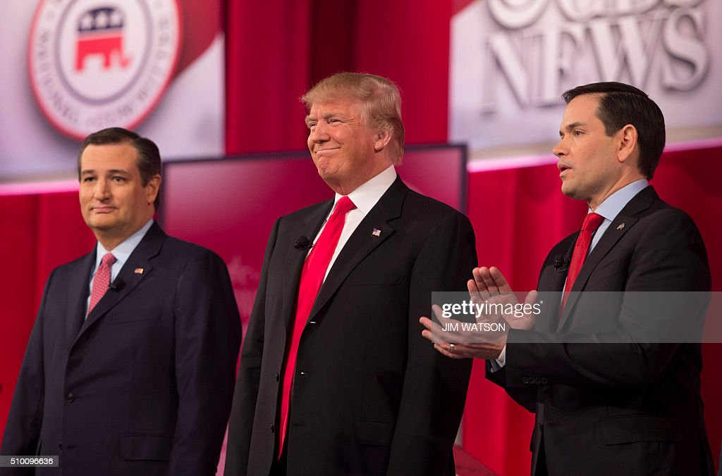 Republican presidential candidates Ted Cruz (L)and Marco Rubio (R) applaud as fellow candidate Donald Trump (C) is introduced during the CBS News Republican Presidential Debate in Greenville, South Carolina, February 13, 2016. / AFP / JIM WATSON