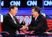 Republican presidential candidates US Rep former US Sen Rick Santorum and former Massachusetts Gov Mitt Romney talk after participating in a debate...