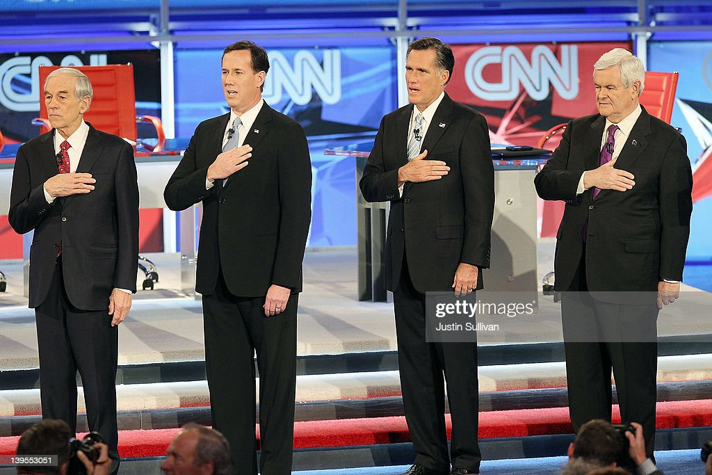 Republican presidential candidates (L-R) U.S. Rep. <a gi-track='captionPersonalityLinkClicked' href=/galleries/search?phrase=Ron+Paul&family=editorial&specificpeople=2300665 ng-click='$event.stopPropagation()'>Ron Paul</a> (R-TX), former U.S. Sen. <a gi-track='captionPersonalityLinkClicked' href=/galleries/search?phrase=Rick+Santorum&family=editorial&specificpeople=212911 ng-click='$event.stopPropagation()'>Rick Santorum</a>, former Massachusetts Gov. <a gi-track='captionPersonalityLinkClicked' href=/galleries/search?phrase=Mitt+Romney&family=editorial&specificpeople=207106 ng-click='$event.stopPropagation()'>Mitt Romney</a>, and former Speaker of the House <a gi-track='captionPersonalityLinkClicked' href=/galleries/search?phrase=Newt+Gingrich&family=editorial&specificpeople=202915 ng-click='$event.stopPropagation()'>Newt Gingrich</a> participate in the Pledge Of Allegiance ahead of a debate sponsored by CNN and the Republican Party of Arizona at the Mesa Arts Center February 22, 2012 in Mesa, Arizona. The debate is the last one scheduled before voters head to the polls in Arizona's primary on February 28 and Super Tuesday on March 6.