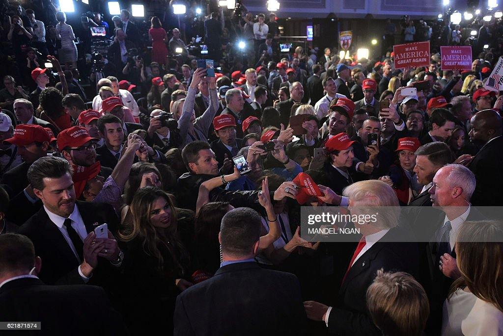 TOPSHOT - Republican presidential elect Donald Trump (3R, down) meets supporters during election night at the New York Hilton Midtown in New York on November 9, 2016. Trump stunned America and the world Wednesday, riding a wave of populist resentment to defeat Hillary Clinton in the race to become the 45th president of the United States. / AFP / MANDEL