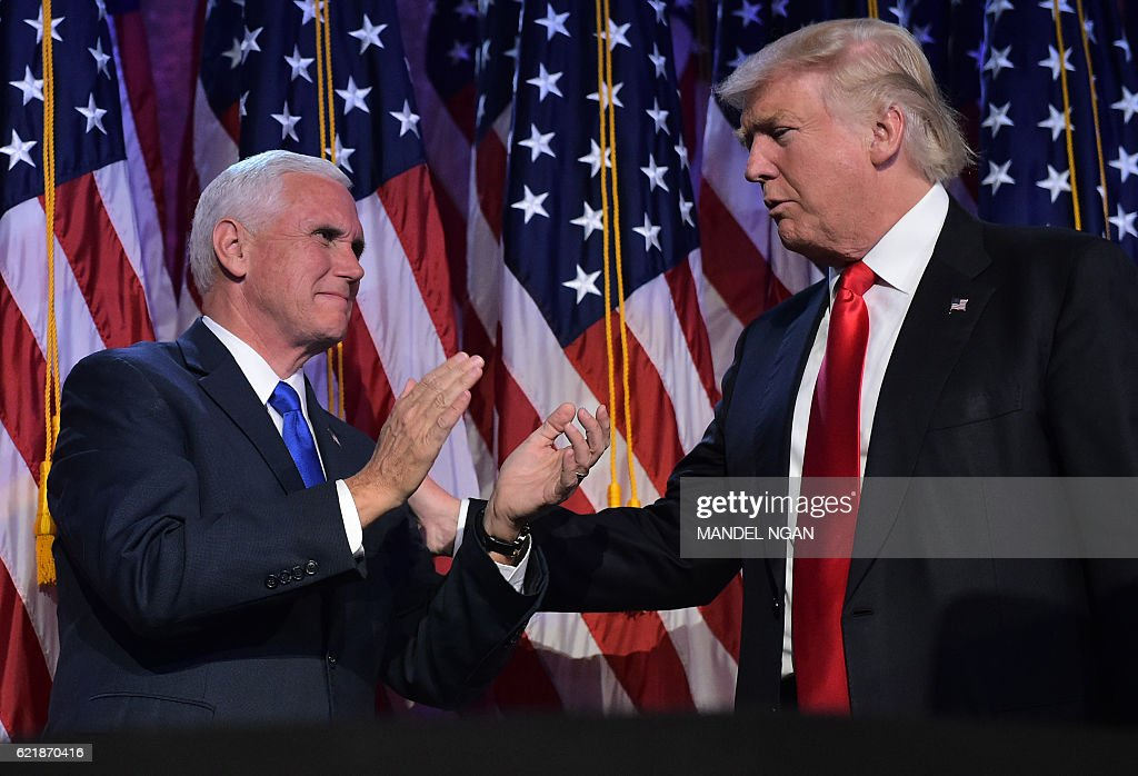Republican presidential elect Donald Trump (R) reaches to his Vice President elect Mike Pence during election night at the New York Hilton Midtown in New York on November 9, 2016. Trump stunned America and the world Wednesday, riding a wave of populist resentment to defeat Hillary Clinton in the race to become the 45th president of the United States. / AFP / MANDEL