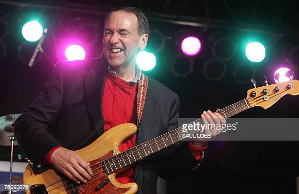 Republican Presidential hopeful and former Arkansas Governor Mike Huckabee plays the guitar with the band the Boogey Woogers during a 'Huck and...