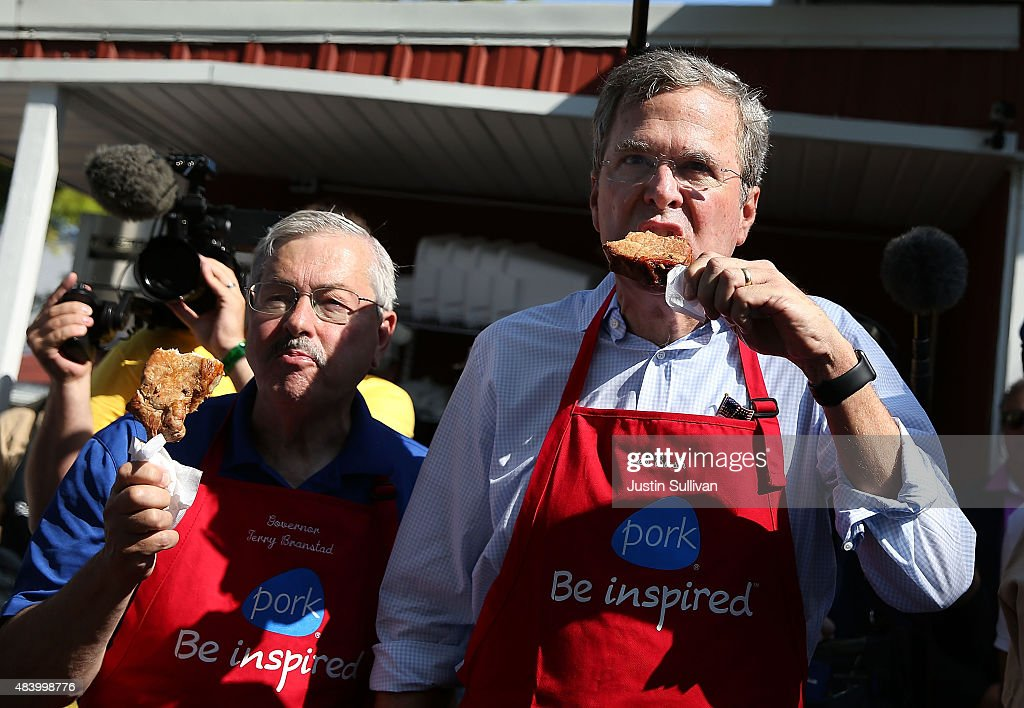 Republican presidential hopeful and former Florida Gov Jeb Bush and Iowa Gov Terry Branstad eat a pork chop on a stick at the Iowa Pork Tent during...