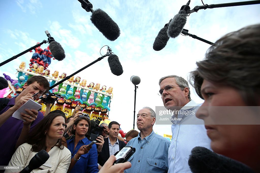 Republican presidential hopeful and former Florida Gov. <a gi-track='captionPersonalityLinkClicked' href=/galleries/search?phrase=Jeb+Bush&family=editorial&specificpeople=171487 ng-click='$event.stopPropagation()'>Jeb Bush</a> (C) talks with members of the media as U.S. Sen. <a gi-track='captionPersonalityLinkClicked' href=/galleries/search?phrase=Chuck+Grassley&family=editorial&specificpeople=504960 ng-click='$event.stopPropagation()'>Chuck Grassley</a> (L) (R-IA) and U.S. Sen. <a gi-track='captionPersonalityLinkClicked' href=/galleries/search?phrase=Joni+Ernst&family=editorial&specificpeople=12731592 ng-click='$event.stopPropagation()'>Joni Ernst</a> (R) (R-IA) look on during the Iowa State Fair on August 14, 2015 in Des Moines, Iowa. Presidential candidates are addressing attendees at the Iowa State Fair on the Des Moines Register Presidential Soapbox stage. The State Fair runs through August 23.