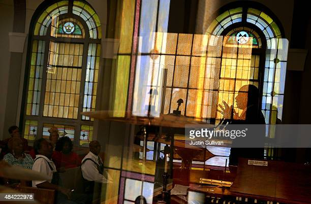 Republican presidential hopeful Ben Carson is seen silhouetted through a window as he speaks during church services at Maple Street Missionary...