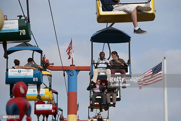 Republican presidential hopeful Ben Carson rides the Sky Glider with a reporter while touring the Iowa State Fair on August 16 2015 in Des Moines...