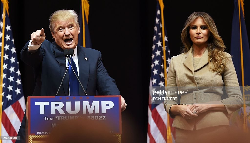 Republican presidential hopeful Donald Trump addresses a rally with his wife Melania on February 8. 2016 in Manchester, NH. US presidential candidates, including billionaire Donald Trump and under-pressure Democrat Hillary Clinton, criss-crossed snowy New Hampshire in a final frantic bit to win over undecided voters before Tuesday's crucial primary. / AFP / Don EMMERT