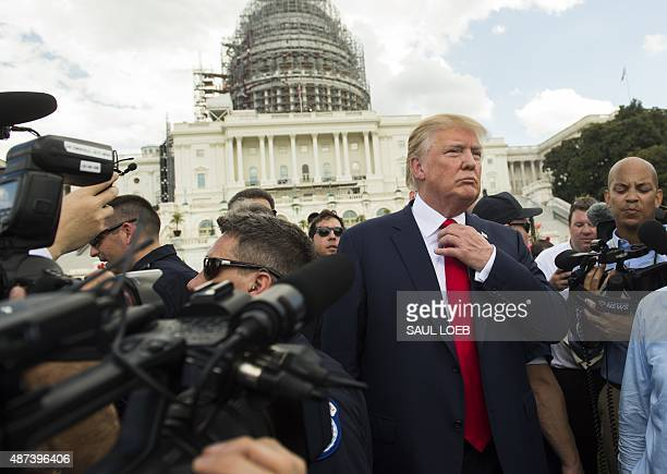 US Republican Presidential hopeful Donald Trump adjusts his tie prior to speaking during a Tea Party rally against the international nuclear...