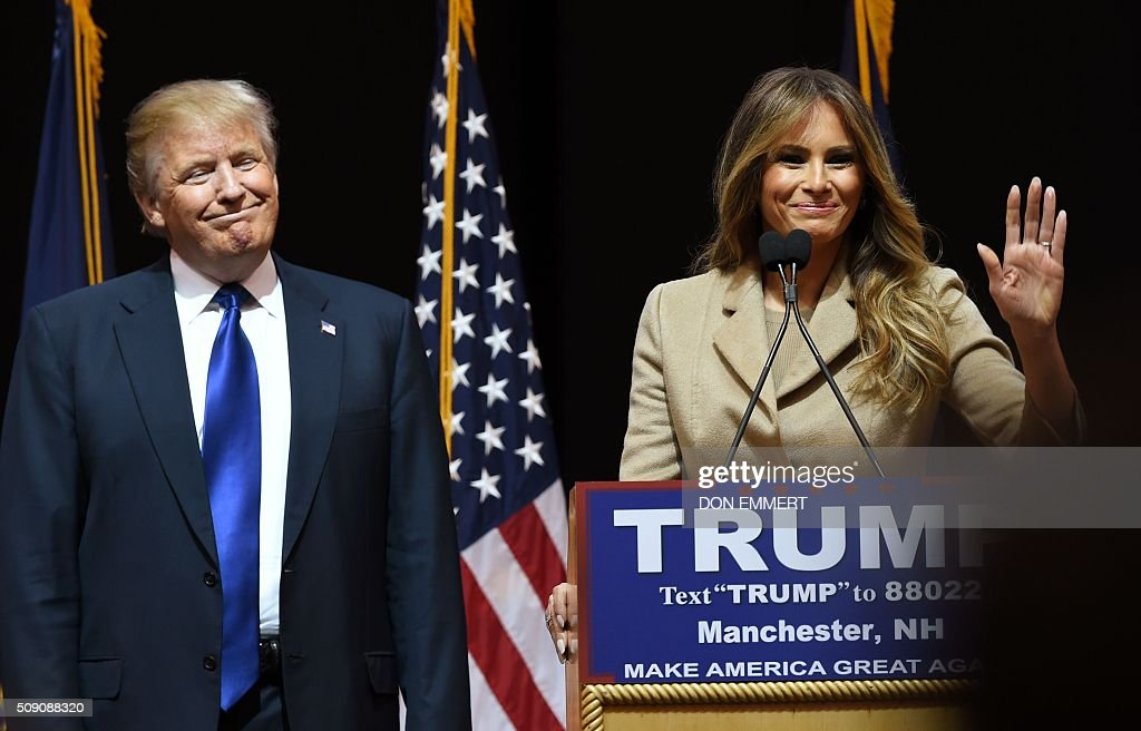 Republican presidential hopeful Donald Trump as his wife Melania speak to the crowd during a rally February 8, 2016 in Manchester, NH. US presidential candidates, including billionaire Donald Trump and under-pressure Democrat Hillary Clinton, criss-crossed snowy New Hampshire in a final frantic bit to win over undecided voters before Tuesday's crucial primary. / AFP / Don EMMERT