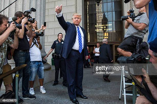 Republican Presidential hopeful Donald Trump gives the thumbs up as he arrives at Manhattan Supreme Court to report for jury duty on August 17 2015...