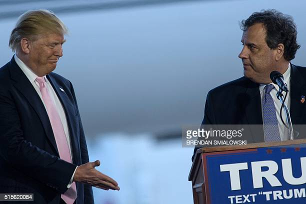 US Republican presidential hopeful Donald Trump reaches to shake the hand of New Jersey Governor Chris Christie after an introduction during a rally...