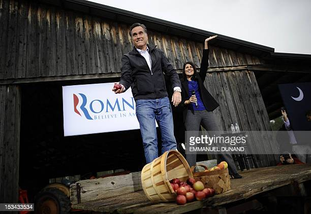 Republican presidential hopeful Mitt Romney tosses apples to supporters as he holds a campaign rally at Harmon's Tree Farm in Gilbert South Carolina...