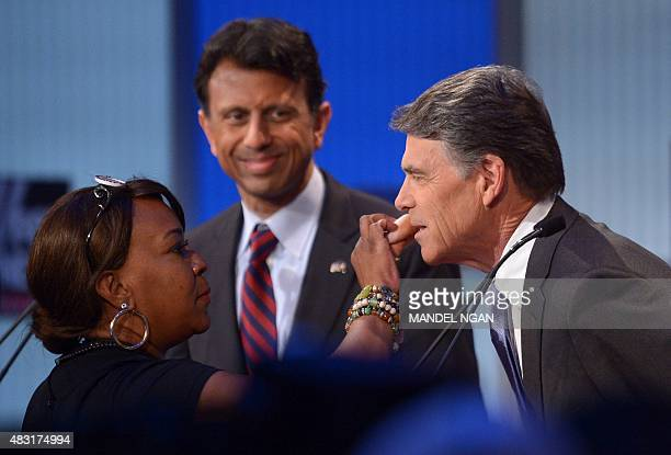 Republican presidential hopeful Rick Perry has makeup applied while opponent Bobby Jendal watches during the Republican presidential primary debate...