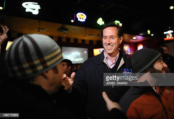 Republican presidential hopeful Rick Santorum greets dinners at a local restaurant as he arrives to campaign and watch a football game in Ames Iowa...
