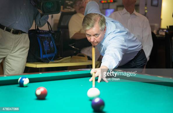 Republican presidential hopeful Sen Lindsey Graham plays a game of pool following a campaign stop at Veteran of Foreign Wars Post 1623 on June 5 2015...